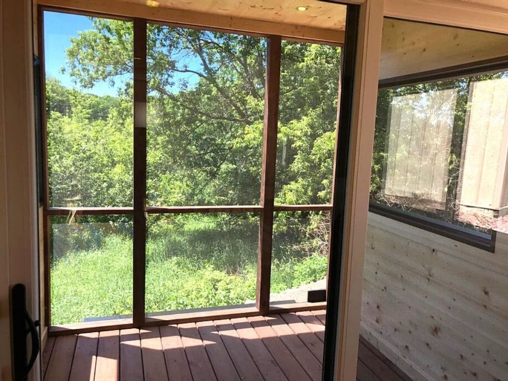 Floor to ceiling windows in enclosed porch of tiny home