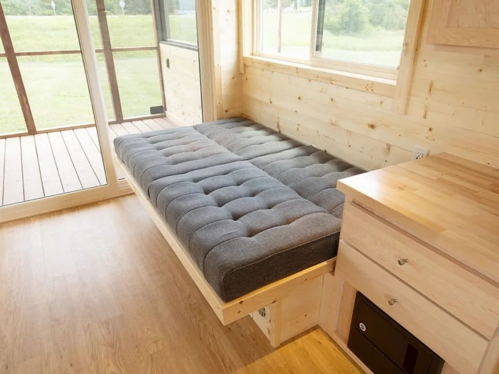 Gray sofa bench laid down into bed with pull out wooden platform