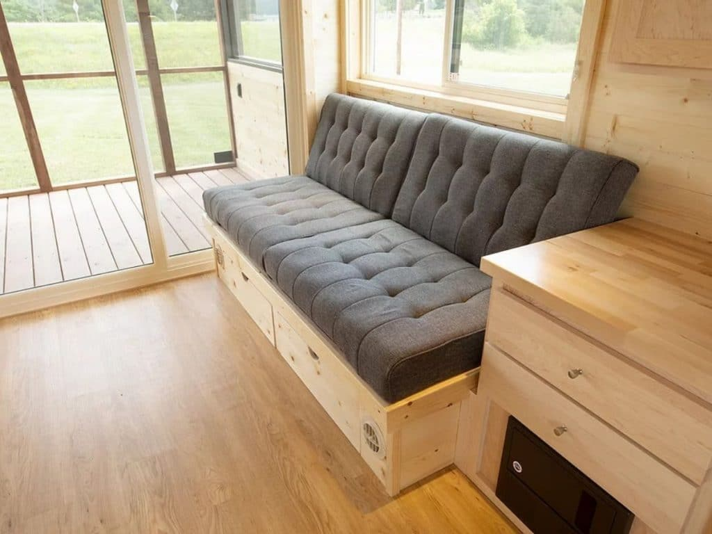Built in sofa with gray cushions against wall below windows