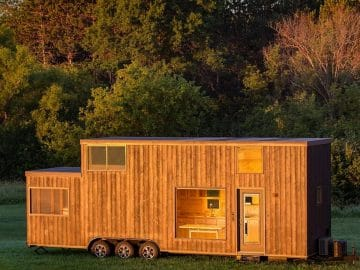 Escape one tiny home with wood siding in field with flowers