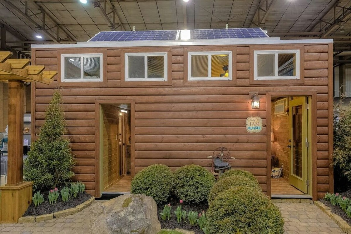 Log cabin style tiny home with two doors on front below row of windows
