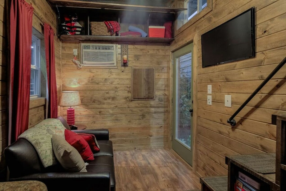 View from kitchen into tiny home living area with log cabin walls and black sofa