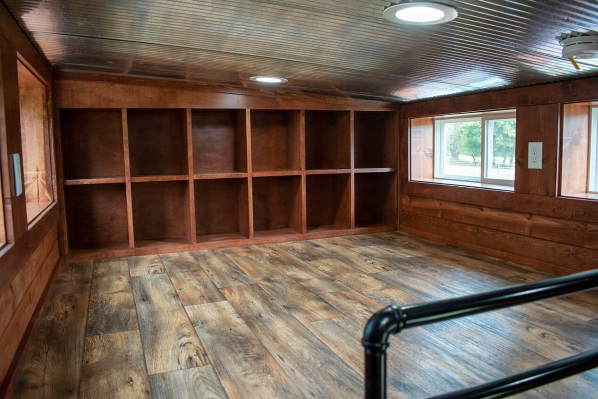Loft with dark wood cubbies built into back wall