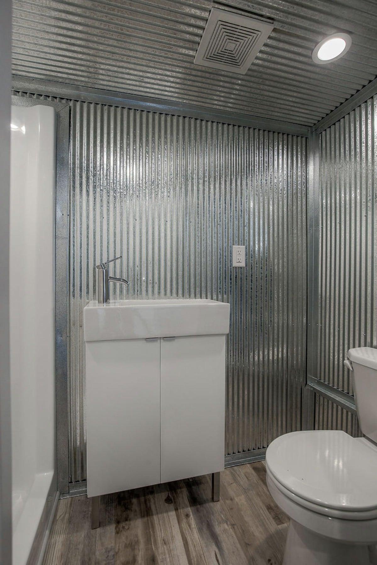 Corrugated metal wall with wood floor in bathroom
