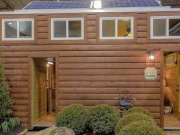 Tiny house with log siding and windows across top half of home
