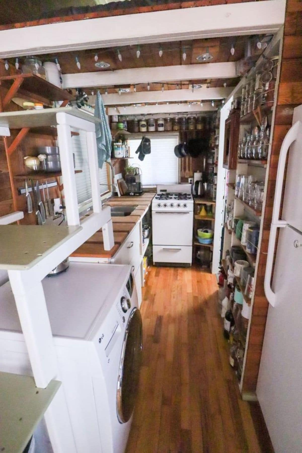 View into kitchen with storage shelves beside white refrigerator