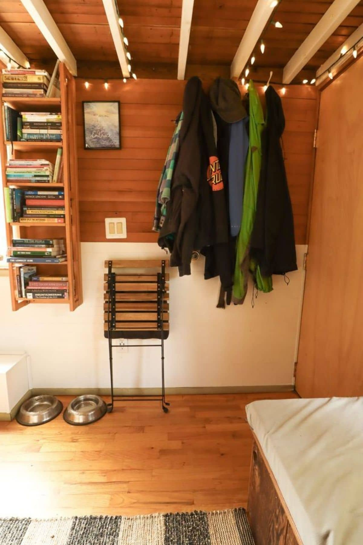 Tiny home entry with jackets on hook and hanging storage shelf