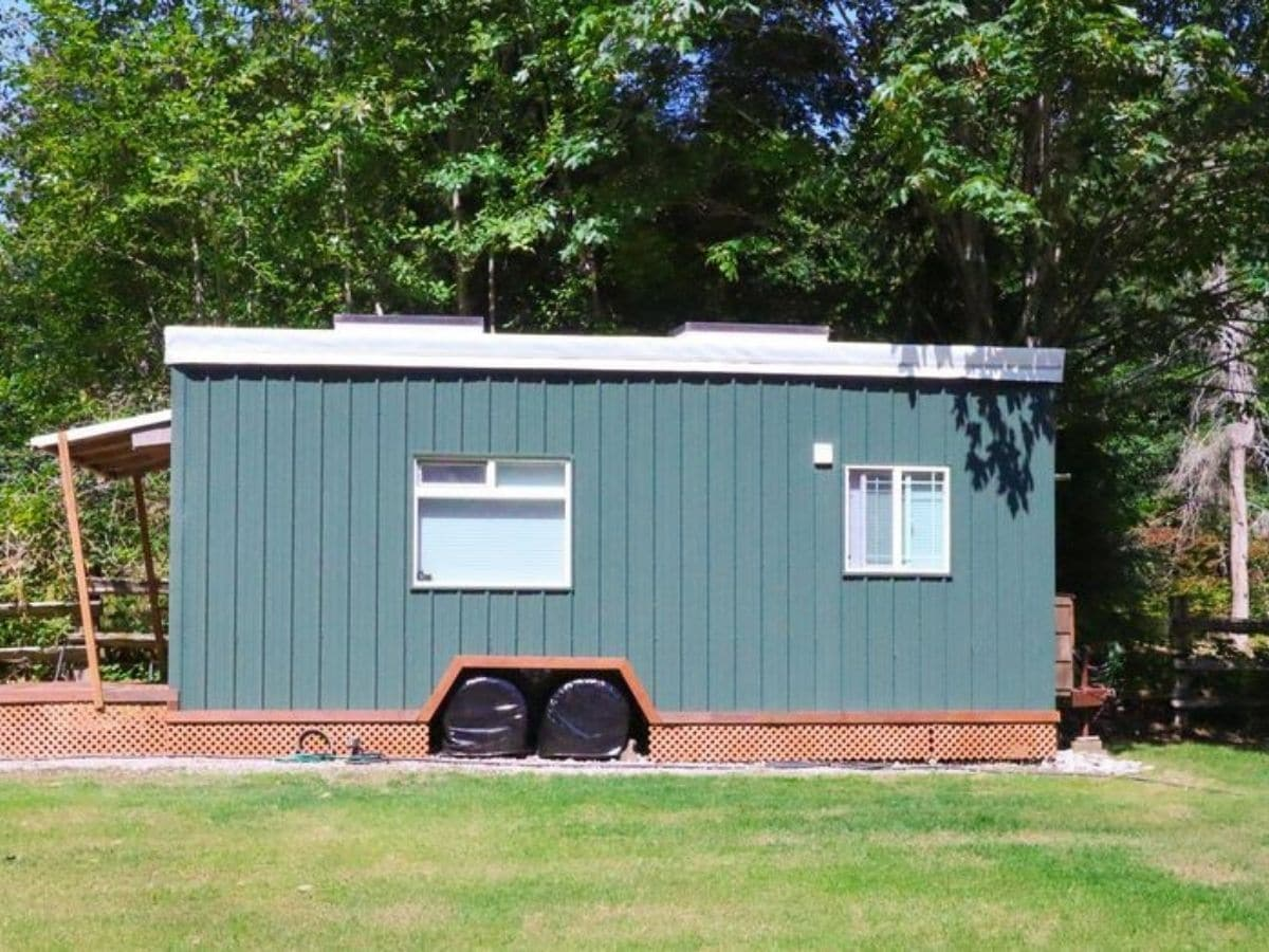 Side of tiny house with two windows inset green siding