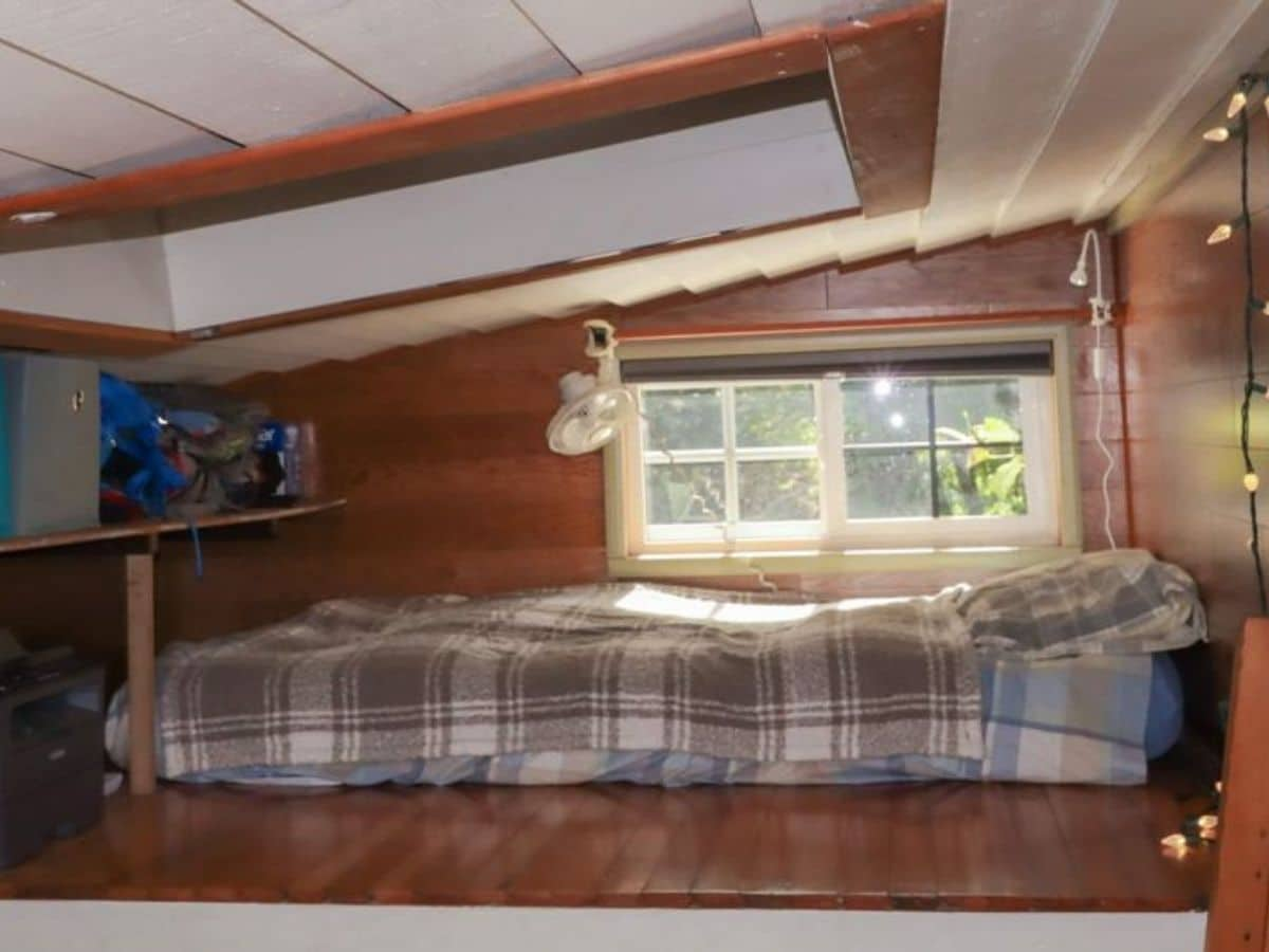 Bed in loft against windows