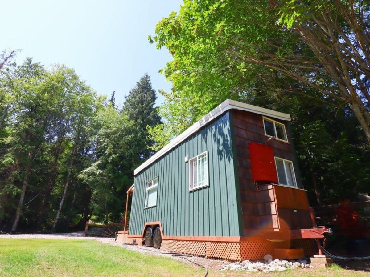 Back side of tiny home with green siding and red accent