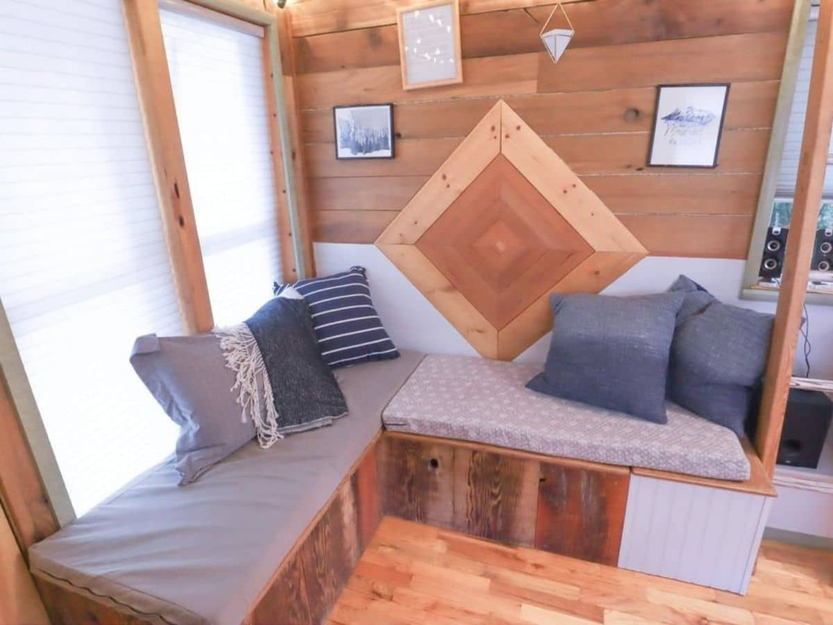 Bench seat with storage underneath in front of wood art on wall
