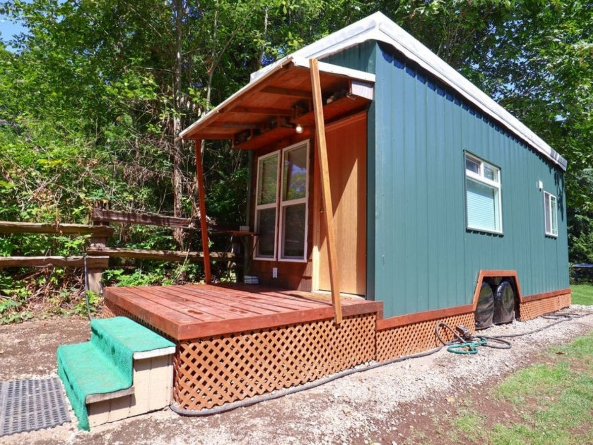 Side of tiny home with porch and green siding