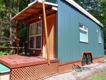 Side of tiny home with green siding
