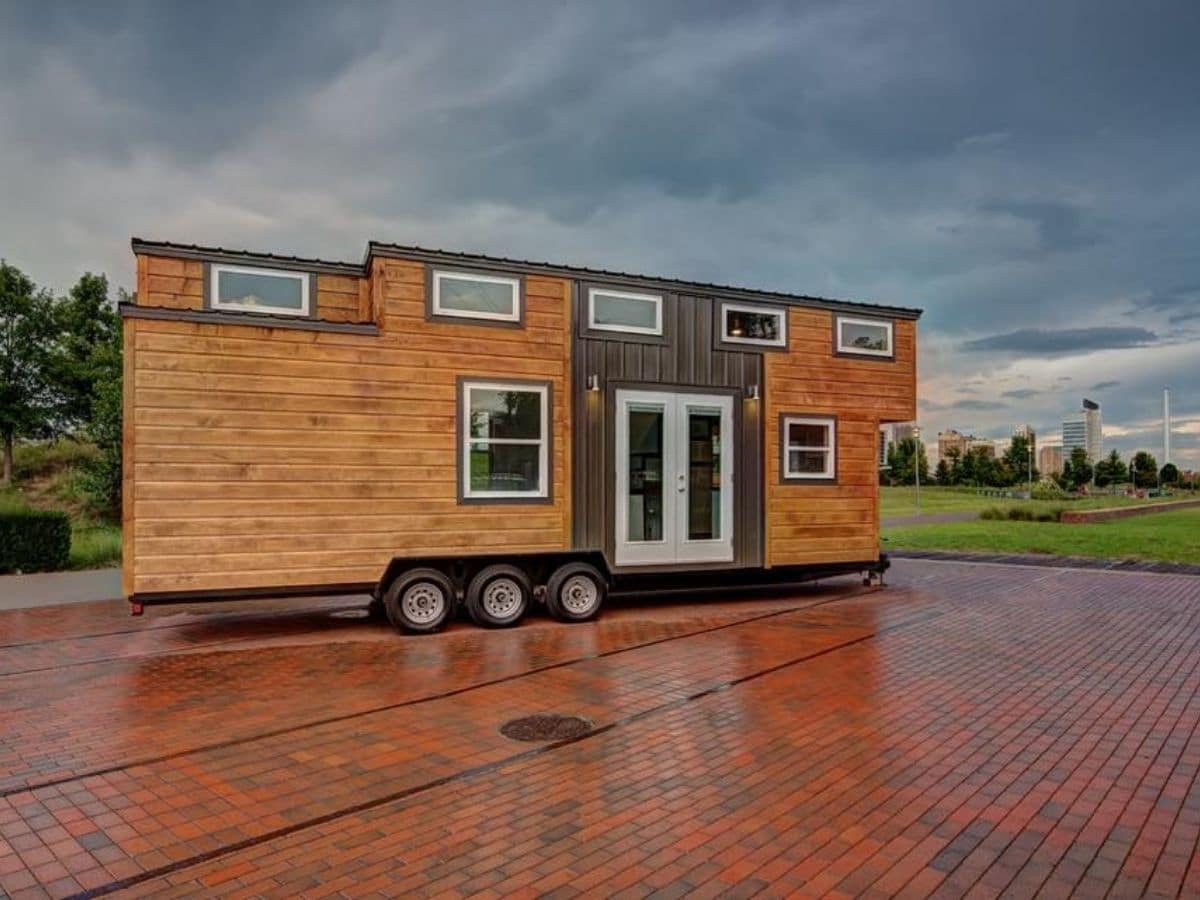Tiny home with triple axel and wood siding on brick lot