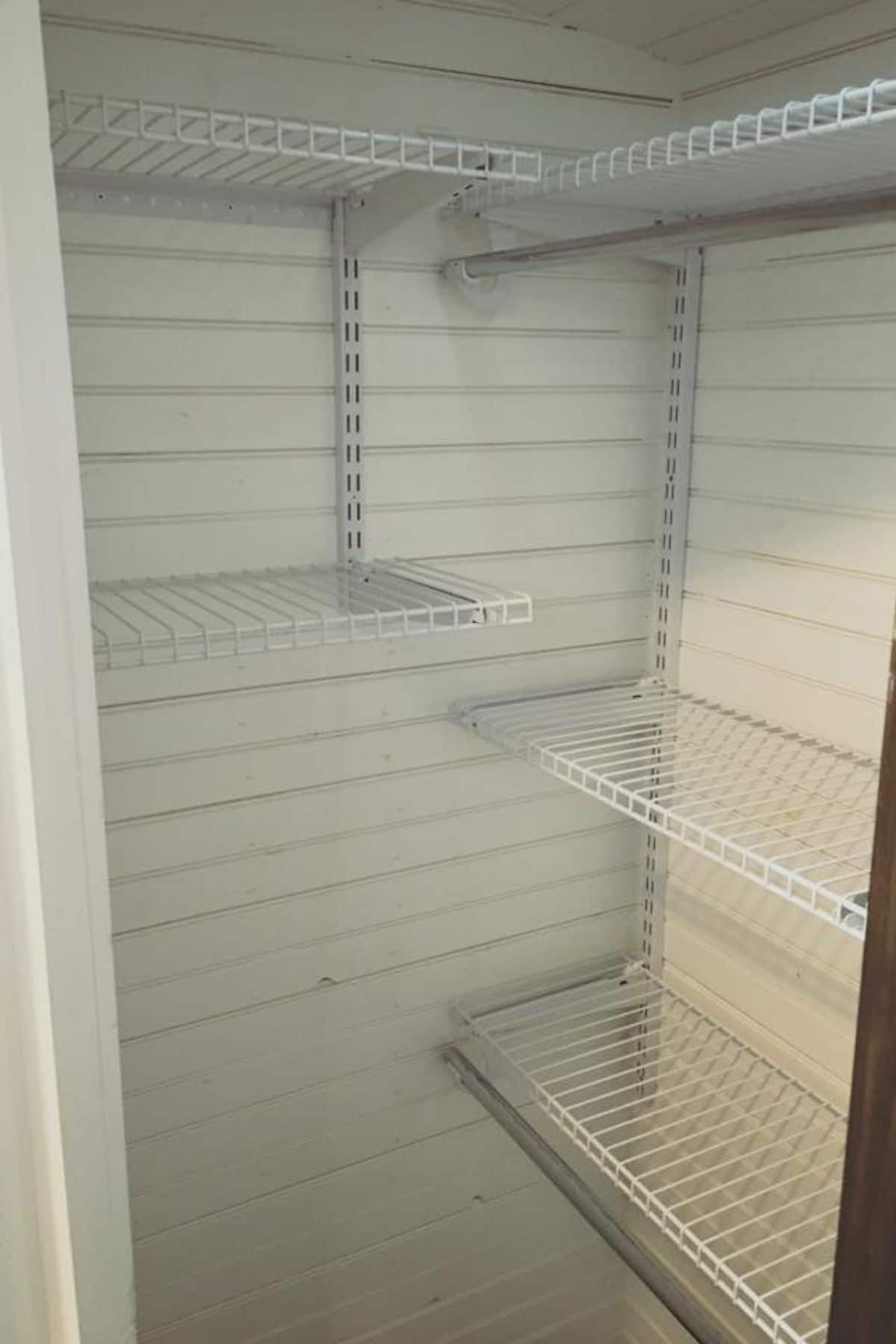 White wall closet with white wire shelves