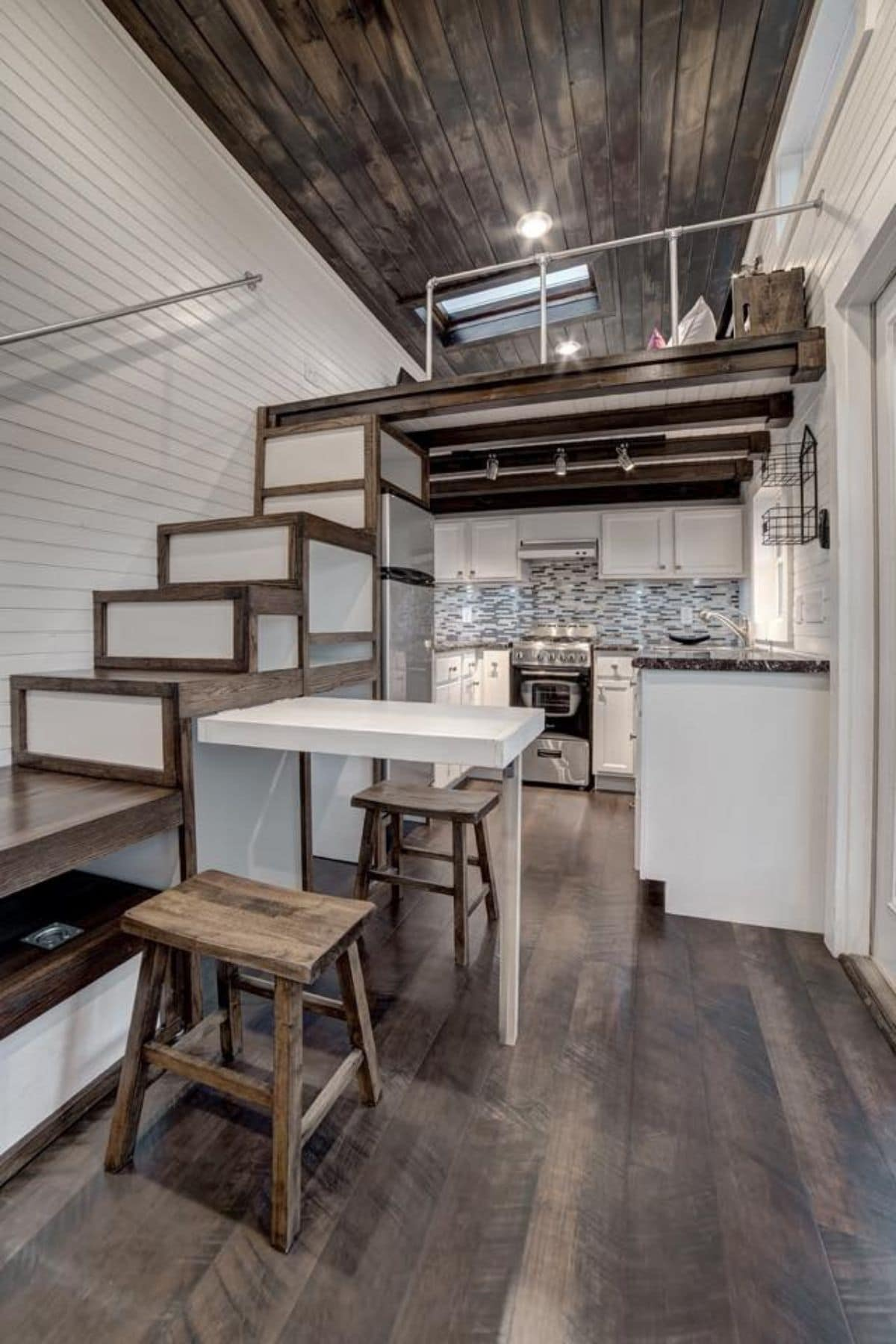 Stairs to loft on left sie of image with pull out table under one stair