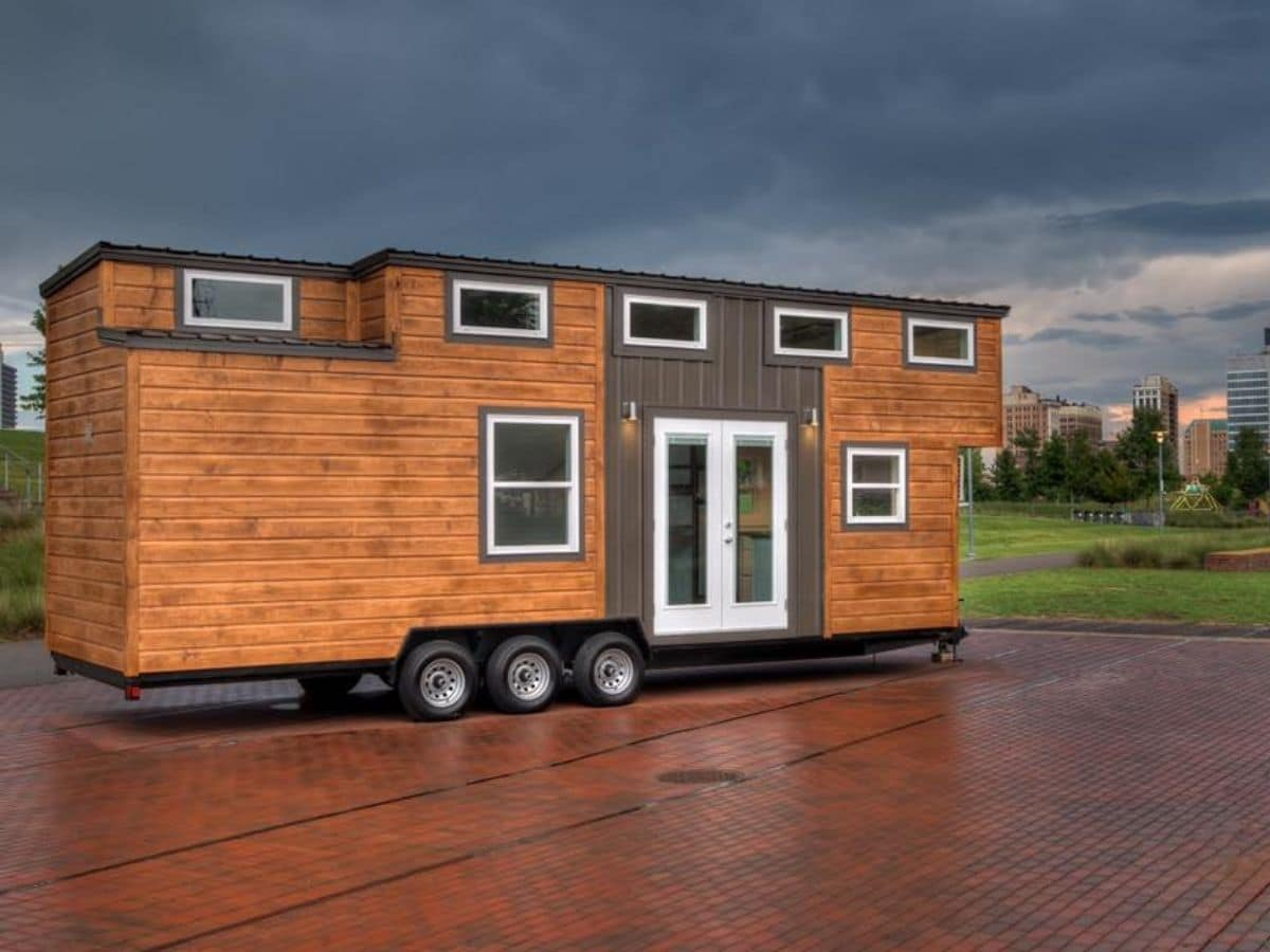 Front of tiny home with wood siding and white french doors