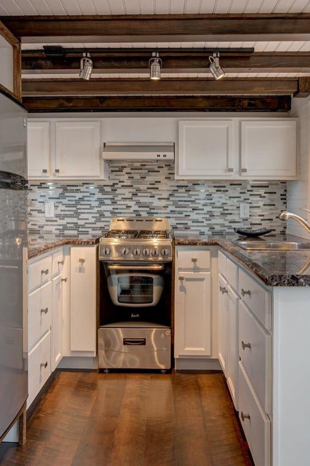 Kitchen with white cabinets and multi colored tile backsplash