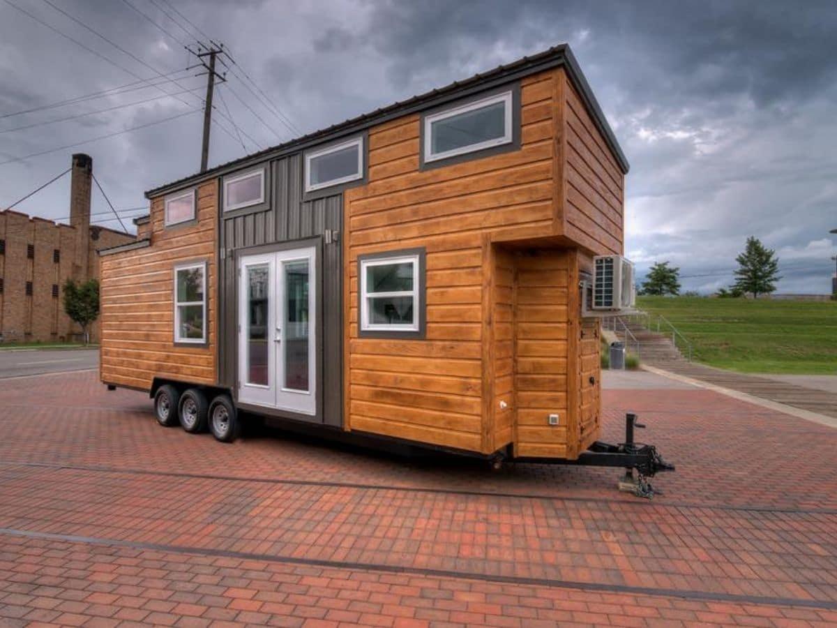 Tiny house on brick road with gray and wood siding