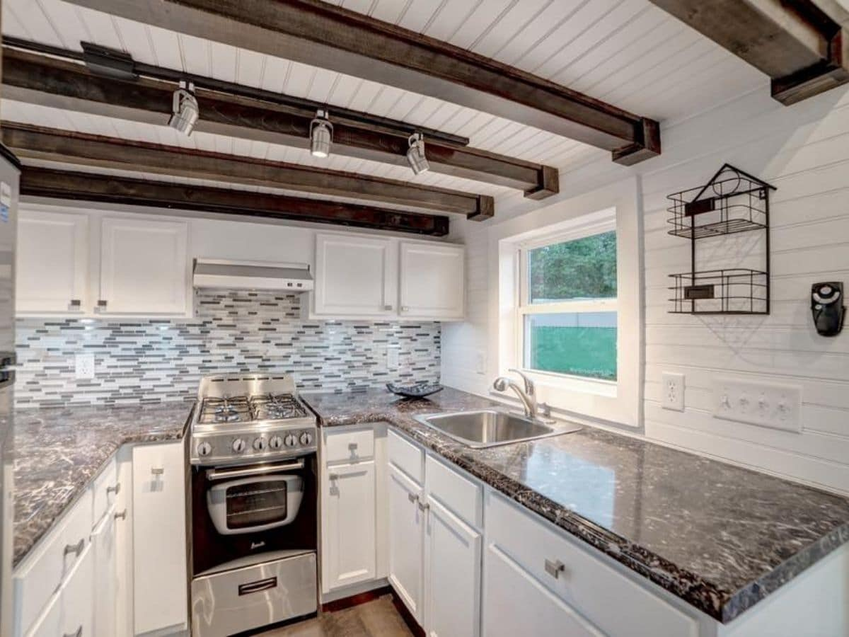 Kitchen with white cabinets stainless steel appliances colorful tile and dark wood accents