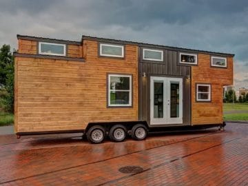 Wood sided long tiny home on triple axel on lot