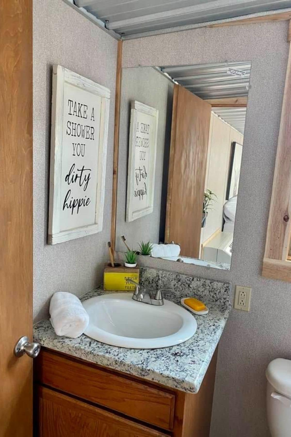 Marble topped vanity with round white sink below long wall mounted mirror