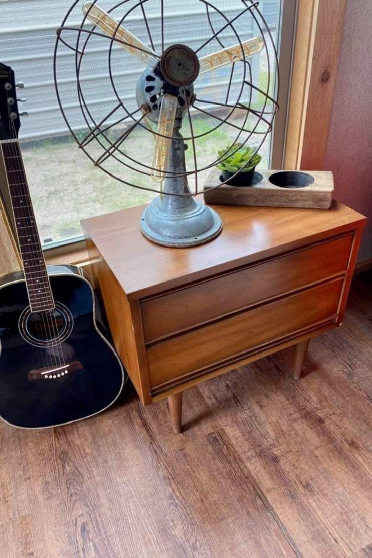 Mid century modern end table with blue fan and guitar next to it below window