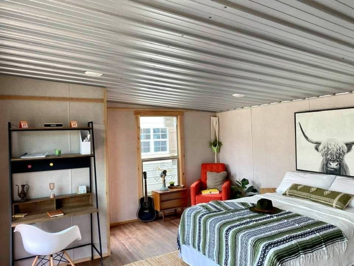 Metal ceiling inside tiny house with striped blanket on bed in foreground