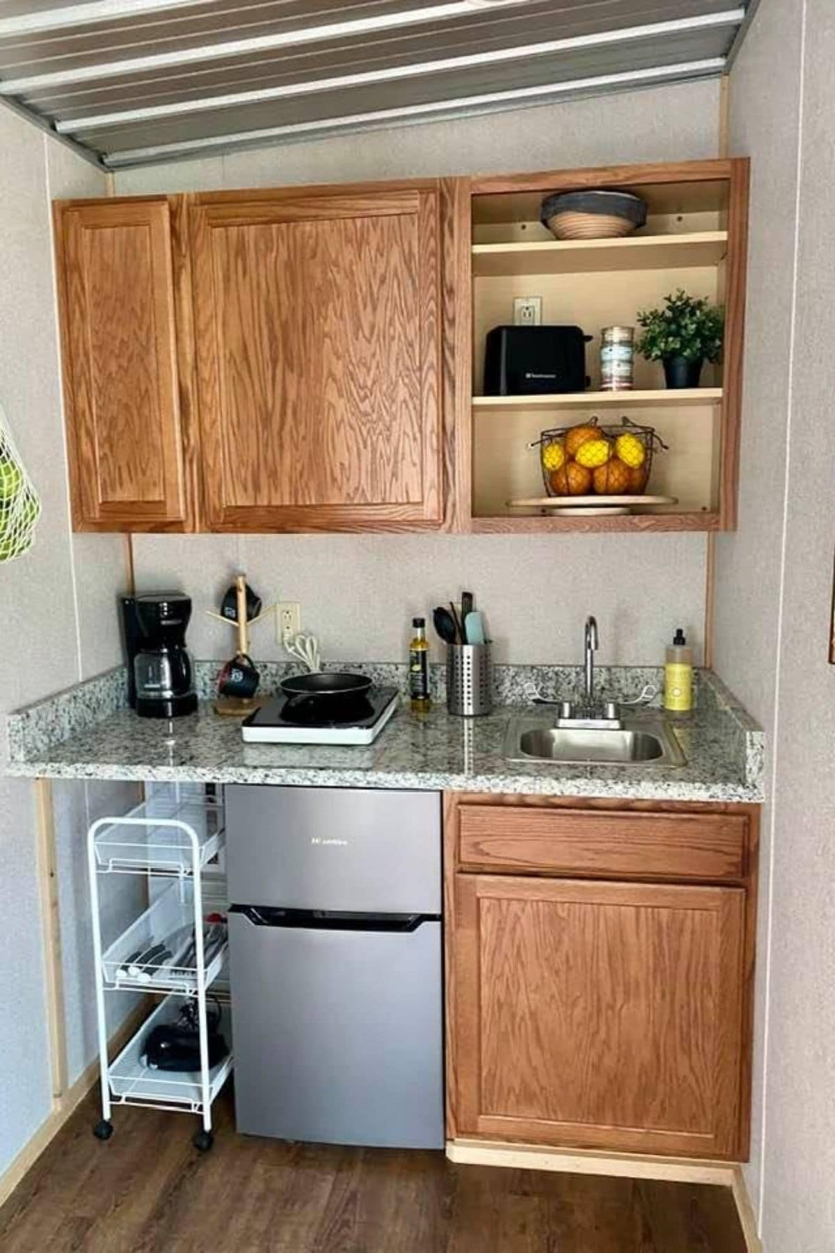 Kitchenette with mini refrigerator under cabinet with light wood doors
