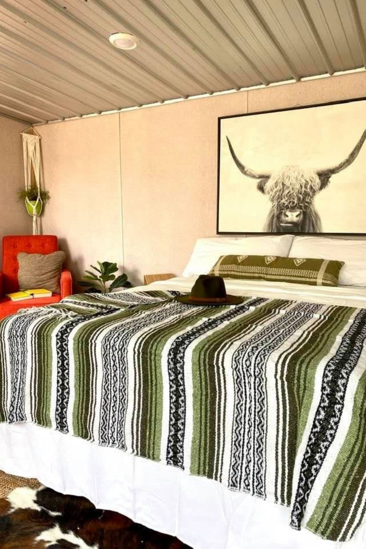 Bed against wall with striped blanket beneath bull decor