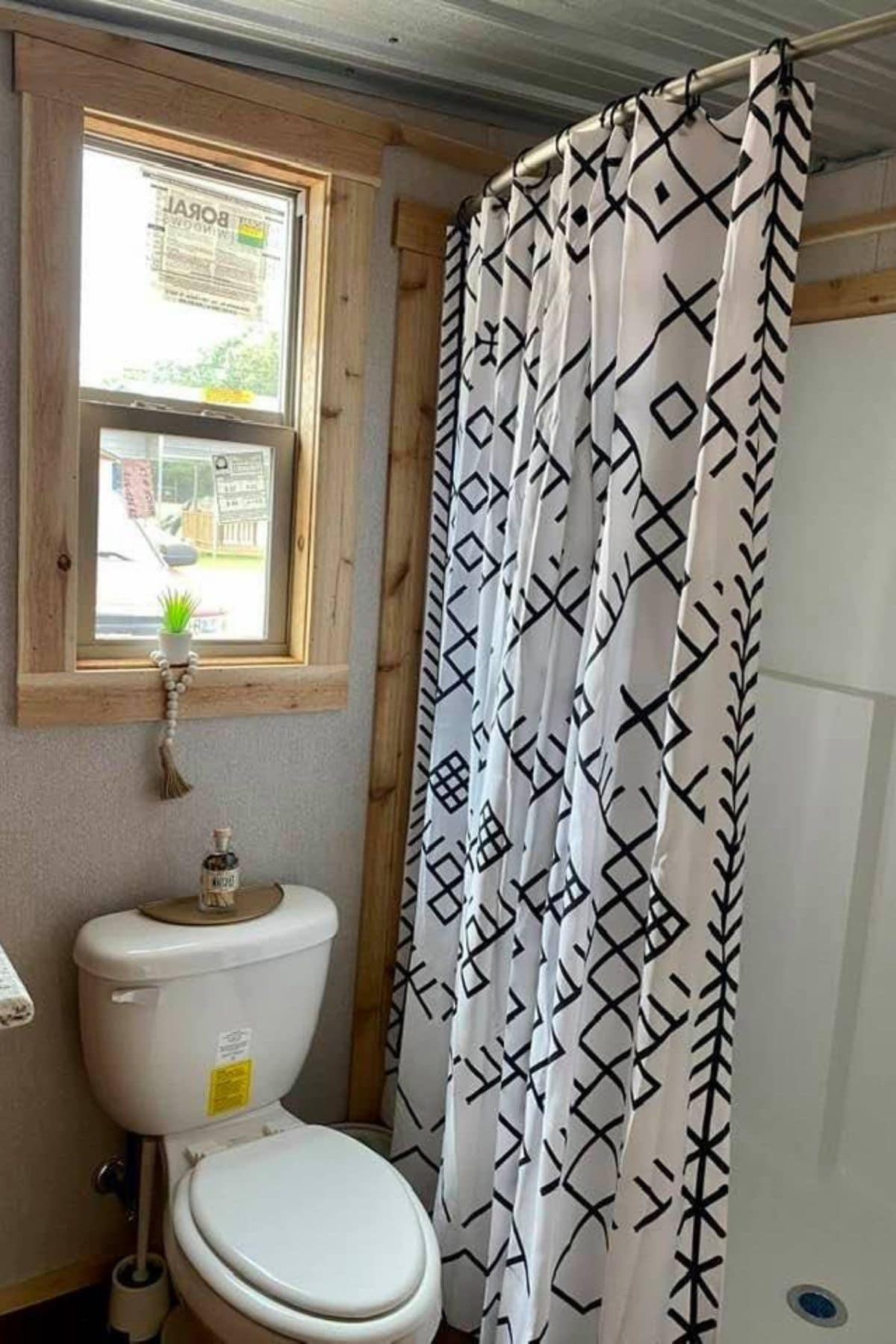 Flush toilet under small window next to shower