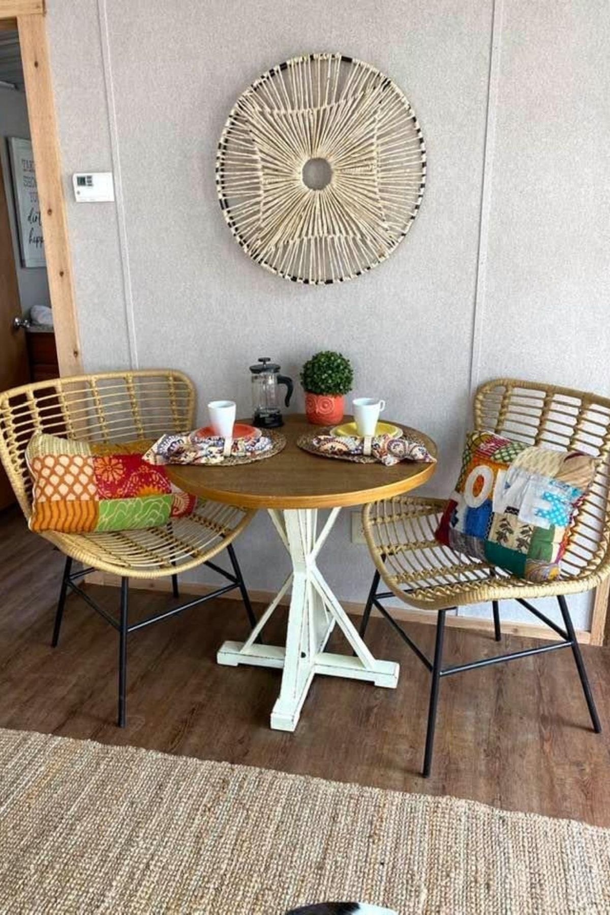 Round table with wicker chairs in front of cream wall with round decor