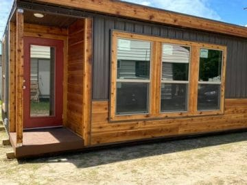 Side of cedar and gray tiny home with three windows and small awning