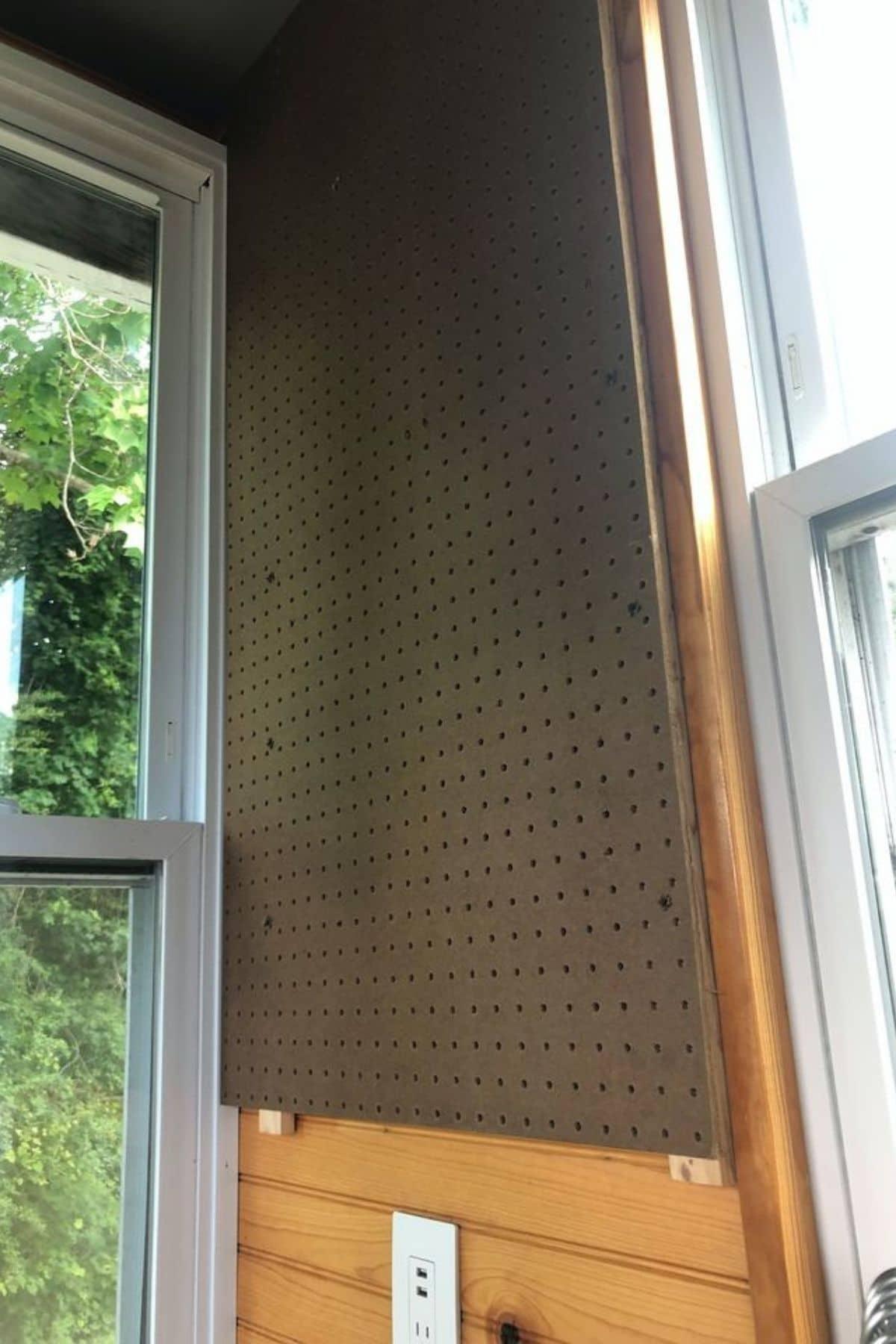 Brown pegboard hanging on wall between windows