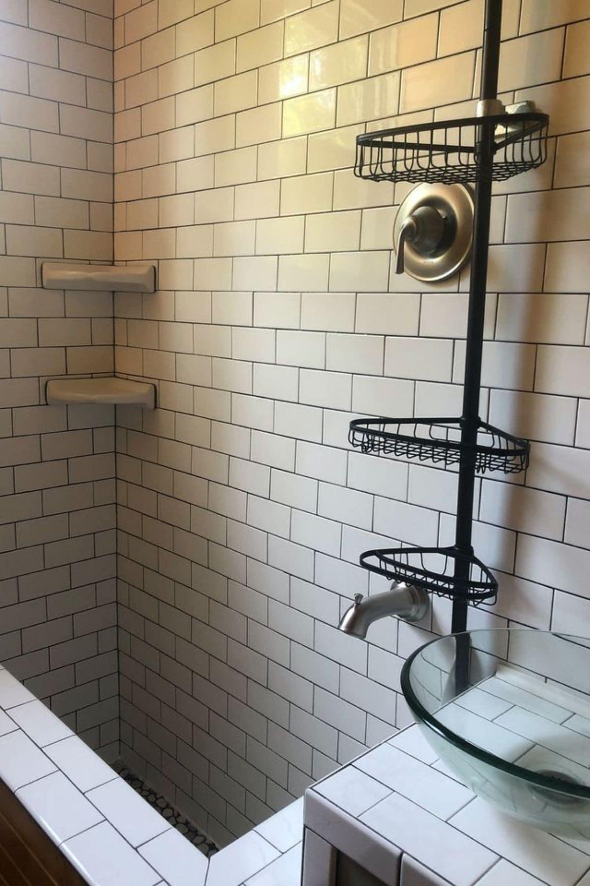 Tiled bathroom shower with wall and black matte hanging basket
