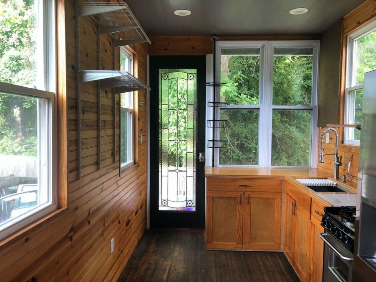 Door into tiny home with wood walls and white 4 pain window on right