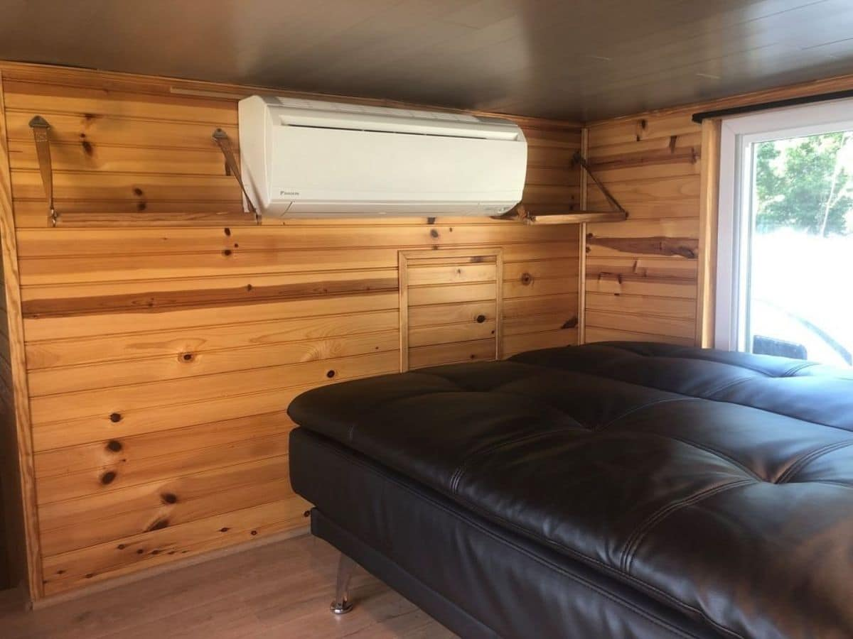Leather sofa against wood wall with white ac unit on wall mount