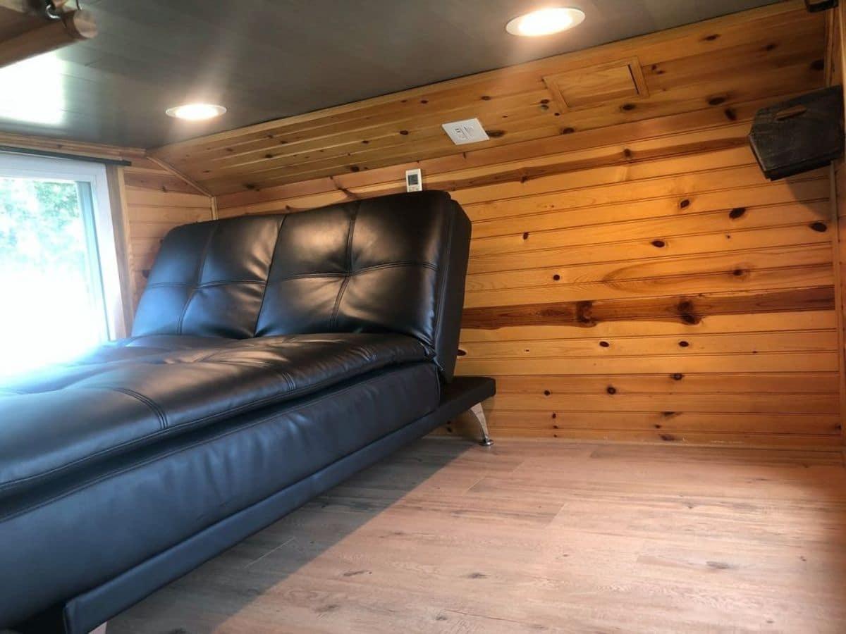 Loft with light wood walls and window next to dark leather futon