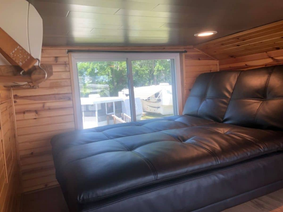 Black leather futon against window