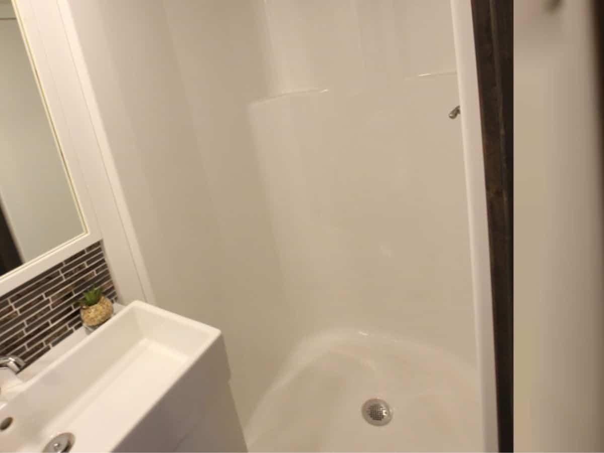 White shower stall next to vanity
