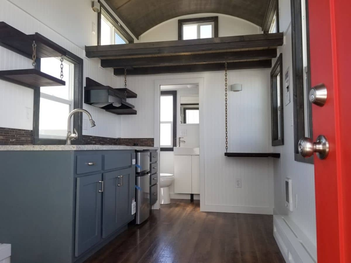 View from red door into tiny home with white walls and dark wood accents