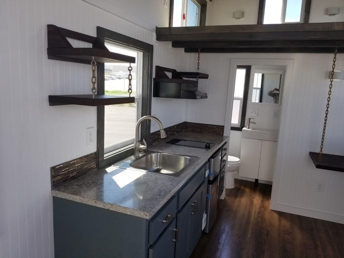 Gray cabinets in kitchenette against white wall with dark walnut accents