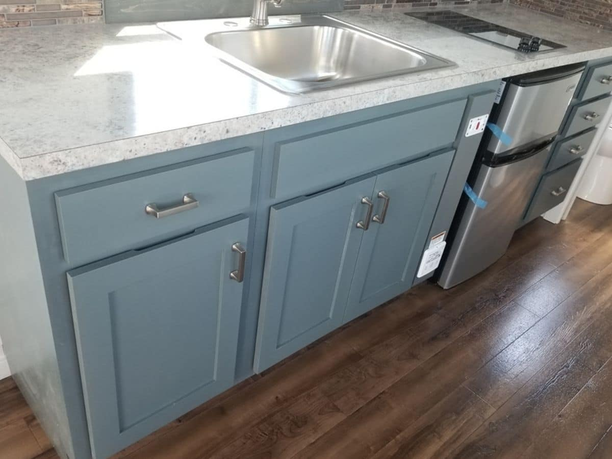Gray cabinets under white marbled countertop