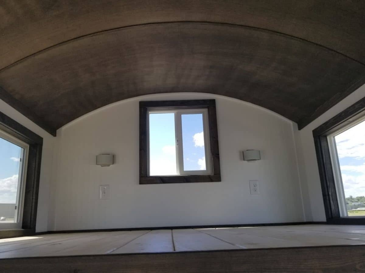 Back wall of loft with curved ceiling in walnut with white walls
