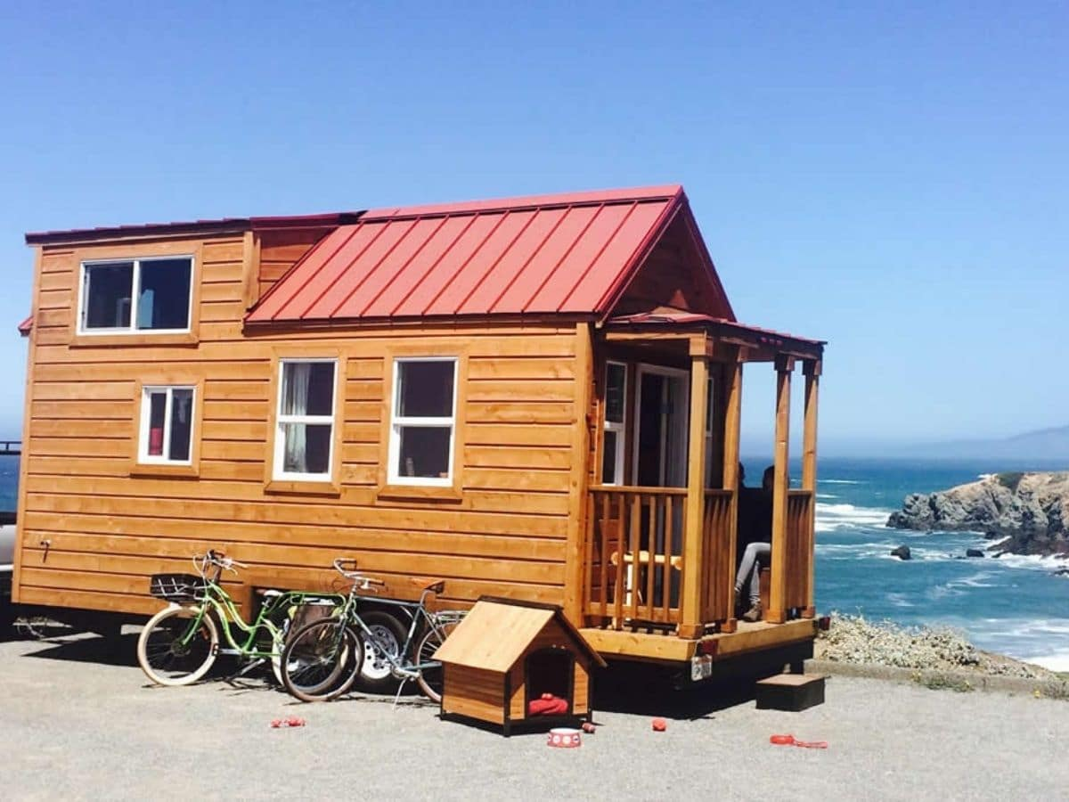 Tiny home next to water on beach with wood siding and red roof