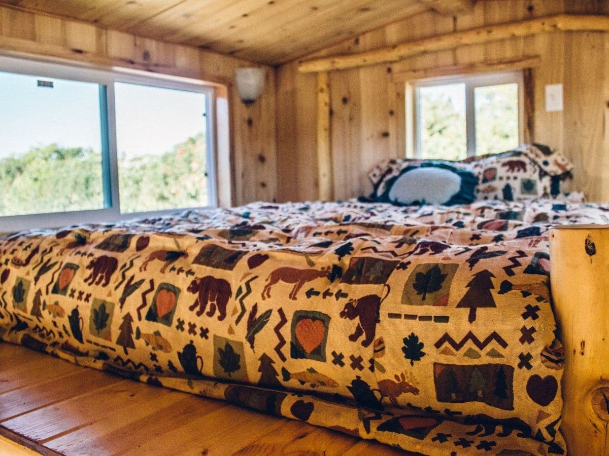 Bed with woodsy comforter in log cabin style loft