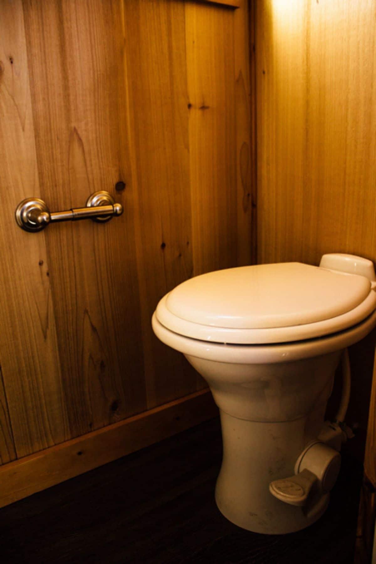White flush toilet against wooden paneling in bathroom