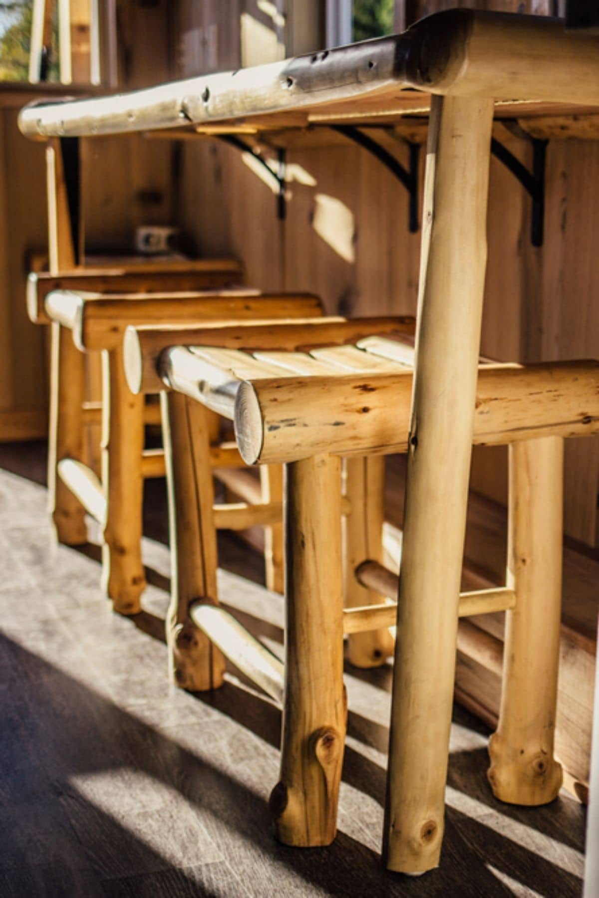 Rustic wooden bar stools in a row under counter