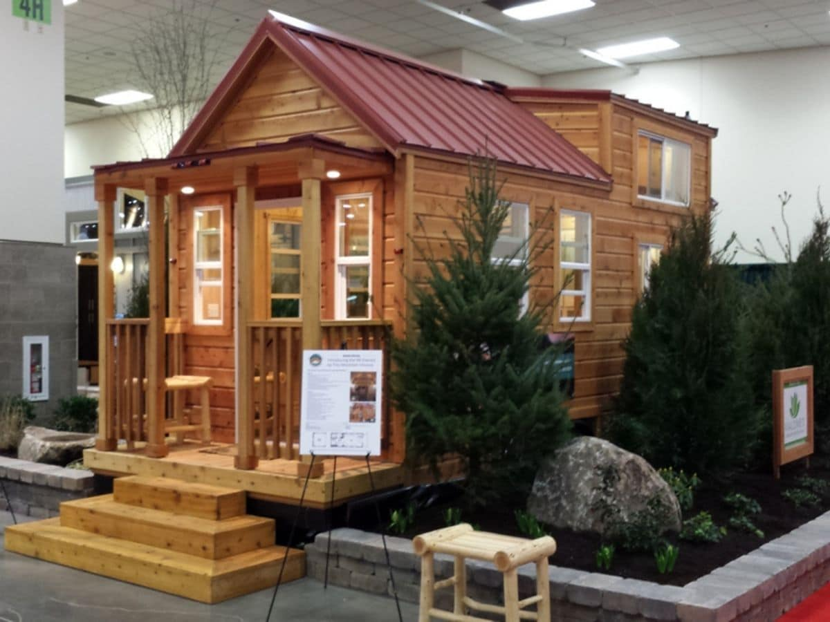 Log cabin tiny house with red roof in show room with fake trees on the side