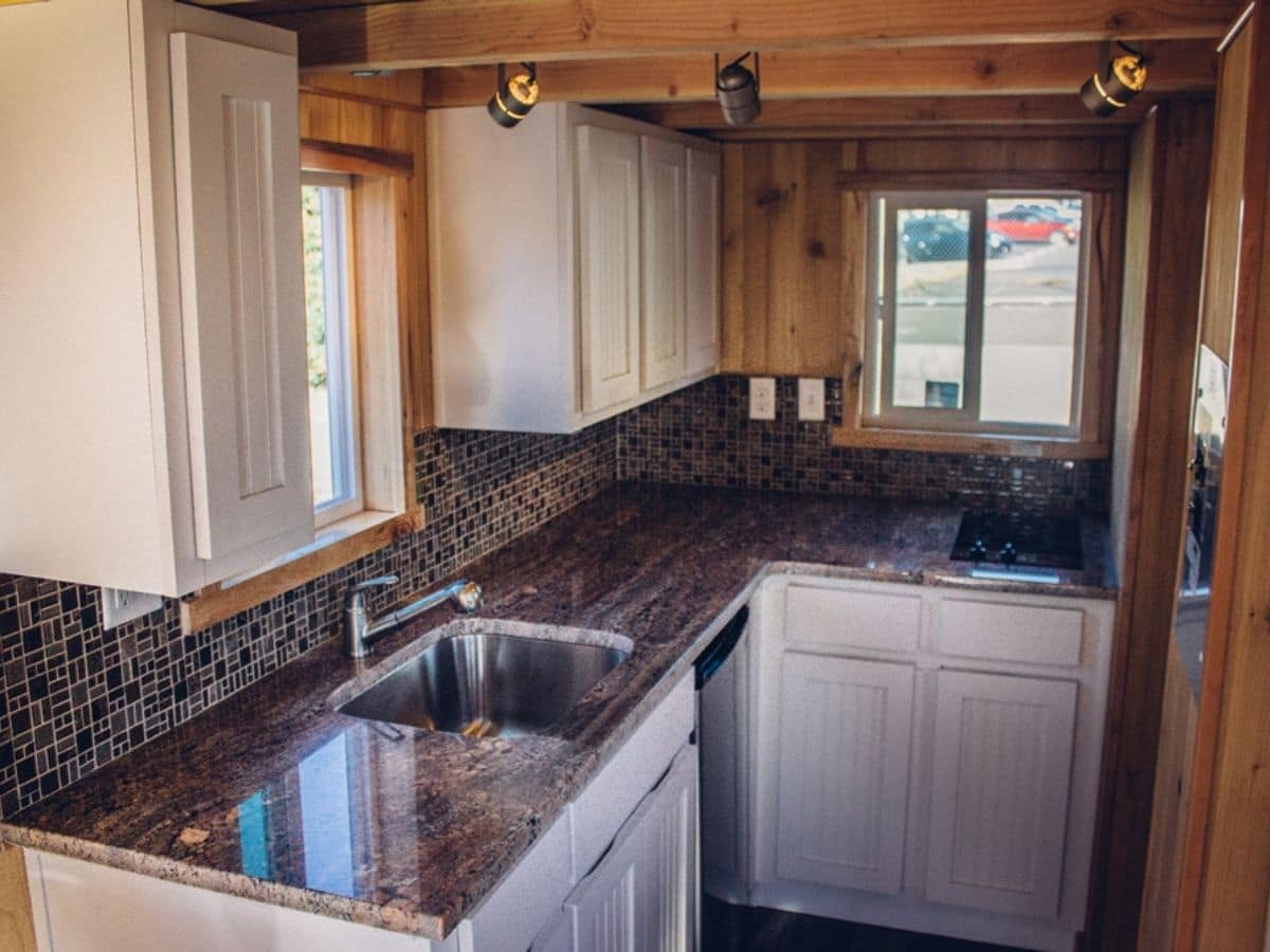 Corner L-shaped kitchen with white cabinets and colorful countertop